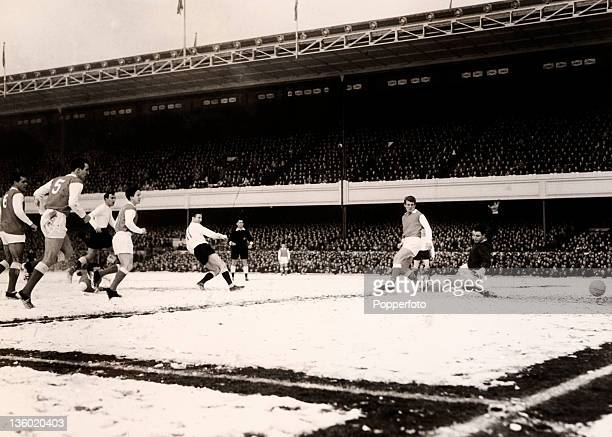 Cliff Jones scores the second goal for Tottenham Hotspur during their Division One match against Arsenal on a snowcovered Highbury pitch in London on...