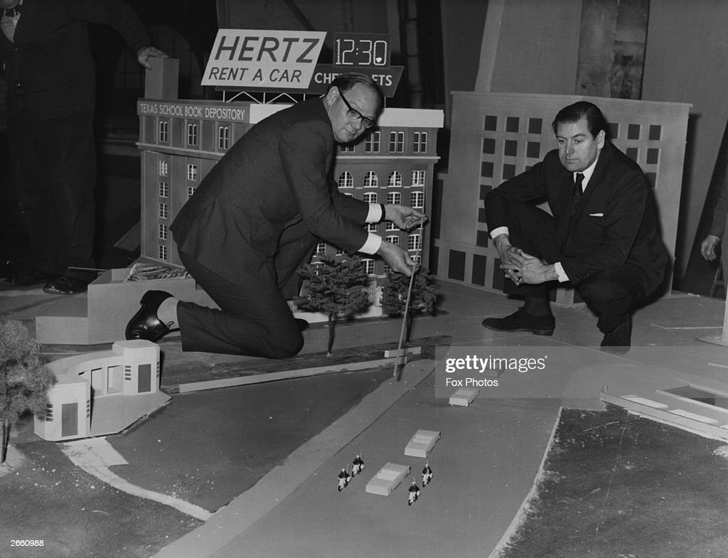 Cliff Michelmore pointing to the path of gun shots which killed President John F Kennedy, on a model reconstruction of the Dealey Plaza, Dallas, in the USA.