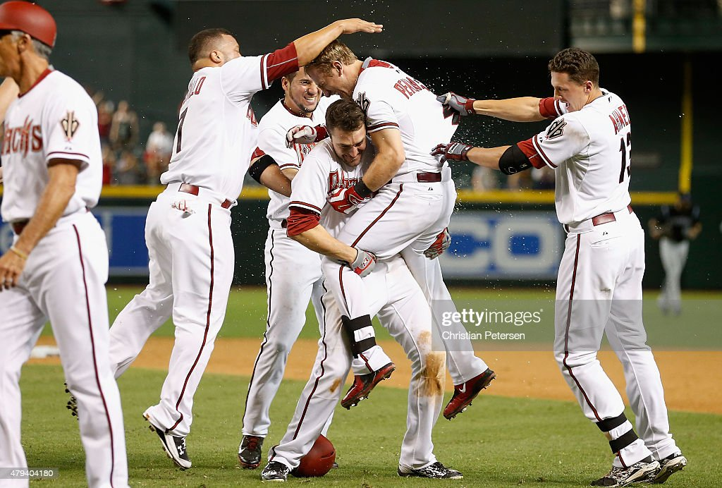 Cliff Pennington #4 of the Arizona Diamondbacks is congratulated by A.J. Pollock #11, David Peralta #6, Nick Ahmed #13 and Welington Castillo #7 after hitting a walk-off sacrifice fly to defeate the Colorado Rockies 4-3 in the 11th inning of the MLB game at Chase Field on July 3, 2015 in Phoenix, Arizona.