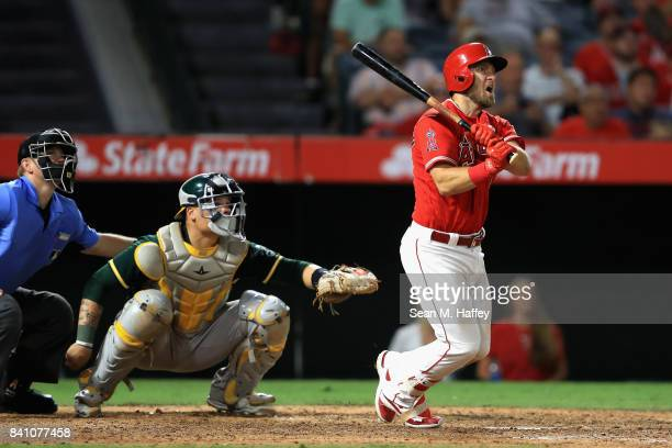 Cliff Pennington of the Los Angeles Angels hits a grand slam homerun as Bruce Maxwell of the Oakland Athletics looks on during the seventh inning of...