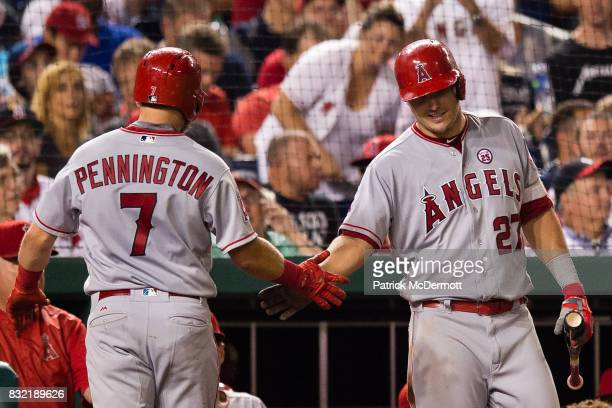 Cliff Pennington of the Los Angeles Angels of Anaheim celebrates with Mike Trout after hitting a solo home run in the eighth inning during a game...