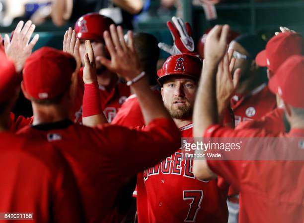 Cliff Pennington of the Los Angeles Angels of Anaheim is congratulated by teammates after scoring on an RBI single hit by CJ Cron during the tenth...