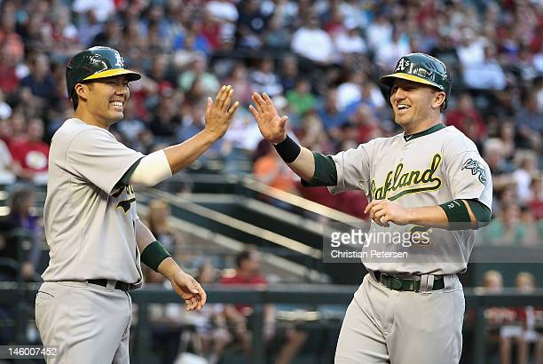 Cliff Pennington of the Oakland Athletics highfives Kurt Suzuki after scoring against the Arizona Diamondbacks during the second inning of the...