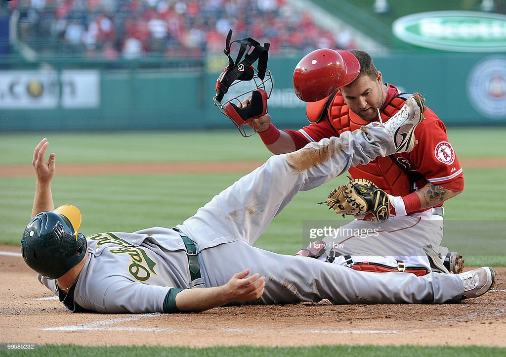 Cliff Pennington #2 of the Oakland Athletics slides home safely to score a run as he collides with Mike Napoli #44 of the Los Angeles Angels during the first inning at Angels Stadium on May 15, 2010 in Anaheim, California.