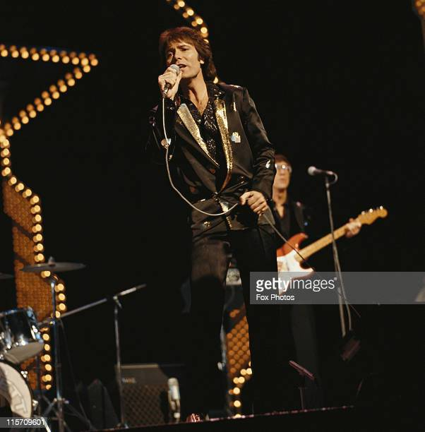 Cliff Richard British pop singer singing into a microphone on stage at the 1981 Royal Variety Performance at the Theatre Royal Drury Lane London...