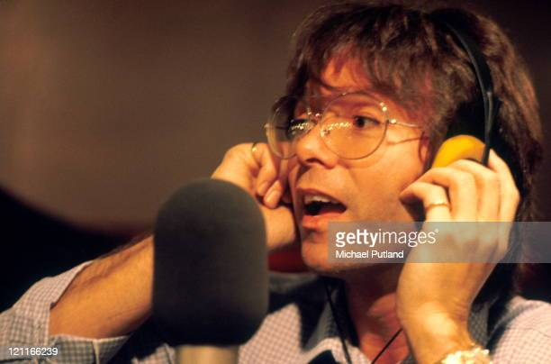 Cliff Richard singing into a microphone in a recording studio, London, 1980.