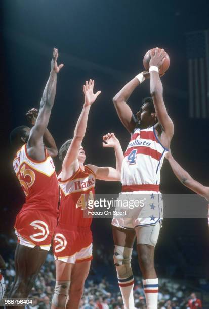 Cliff Robinson of the Washington Bullets shoots over Antoine Carr and Scott Hastings of the Atlanta Hawks during an NBA basketball game circa 1985 at...