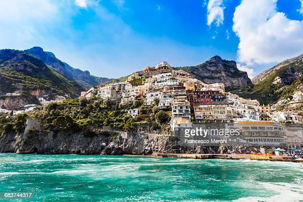 cliff side buildings by sea, positano, amalfi coast, italy - amalfi coast stock photos and pictures