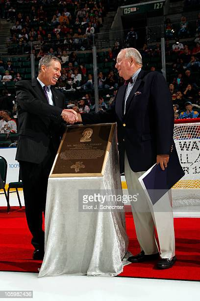Cliff Viner Florida Panthers General Partner shakes hands with Bill Torrey after presenting him with a bronze plaque at a Tribute Night in Torrey's...