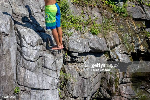 A cliffdiver prepares to dive from a 15 metre rock during the training session of the Cliff Diving European Championship on July 18 2014 in Ponte...
