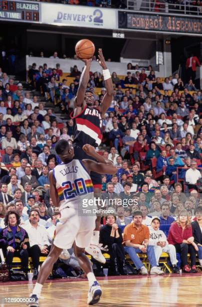 Clifford Robinson, Center and Power Forward for the Portland Trail Blazers attempts the three pointer over LaPhonso Ellis of the Denver Nuggets...