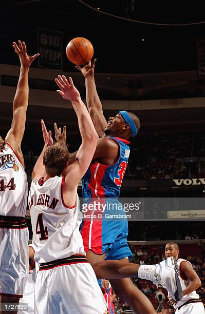 Clifford Robinson of the Detroit Pistons goes up for the shot against Derrick Coleman and Keith Van Horn of the Philadelphia 76ers during the NBA...