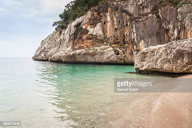 cliffs and beach, cala goloritze, sardinia, italy - cala goloritze foto e immagini stock