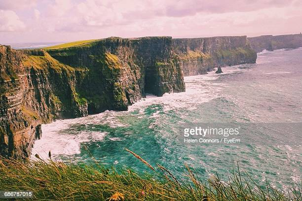 Cliffs Of Moher In Sea Against Cloudy Sky