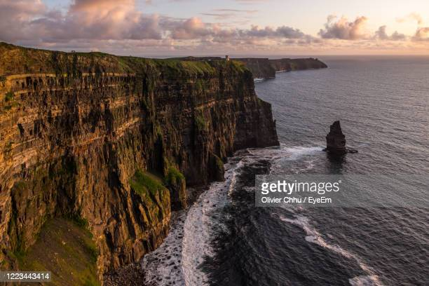 cliffs of moher, ireland - the sunset colors the cliffs in pink and we feel the power of the waves. - sunrise dawn stock pictures, royalty-free photos & images