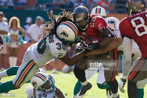Clifton Smith of the Tampa Bay Buccaneers carries the ball and is tackled by Chris Clemons of the Miami Dolphins during a NFL game at Land Shark...