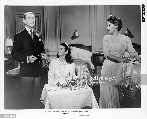 Clifton Webb draws the attention of Audrey Dalton and Barbara Stanwyck as he's holding a fork and knife in a scene from the film 'Titanic' 1953