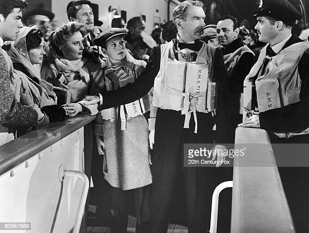 Clifton Webb holds Barbara Stanwyck's arm as he speaks to a ship's officer while Robert Wagner Harper Carter and Audrey Dalton look on in a still...