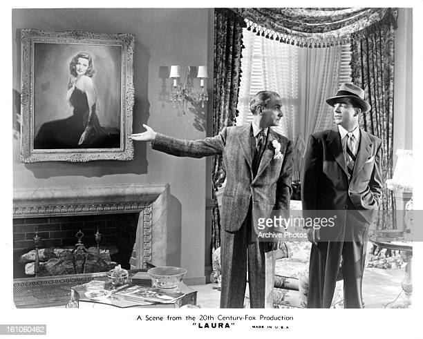 Clifton Webb points to a painting as Dana Andrews looks on in a scene from the film 'Laura' 1944