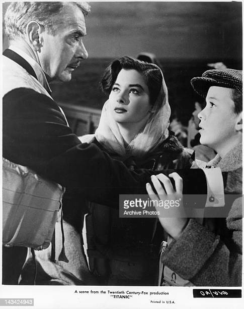Clifton Webb reassuring Audrey Dalton and boy in a scene from the film 'Titanic' 1953
