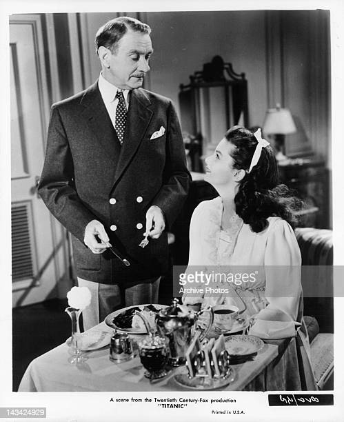 Clifton Webb standing over Audrey Dalton's meal in a scene from the film 'Titanic' 1953