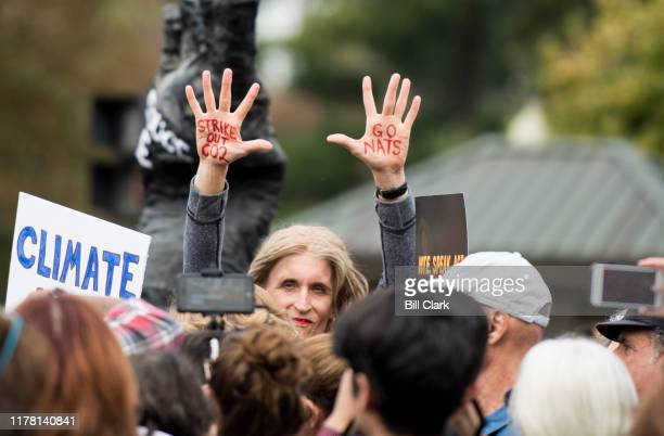 A climate activist and Washington Nationals fan holds up her hands before being arrested during the weekly climate protest at the Capitol on Friday...