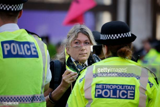 Climate activist from the Extinction Rebellion group holds up a mirror in front of a police officer in the cordon in the middle of Oxford Circus in...