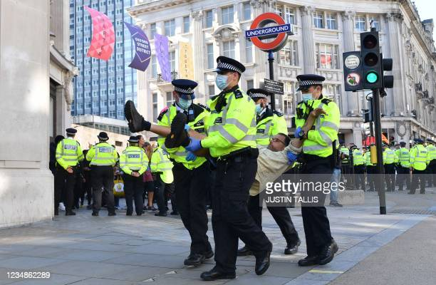 Climate activist from the Extinction Rebellion group is escroted away by police officers from a demonstration blocking the road in the middle of...