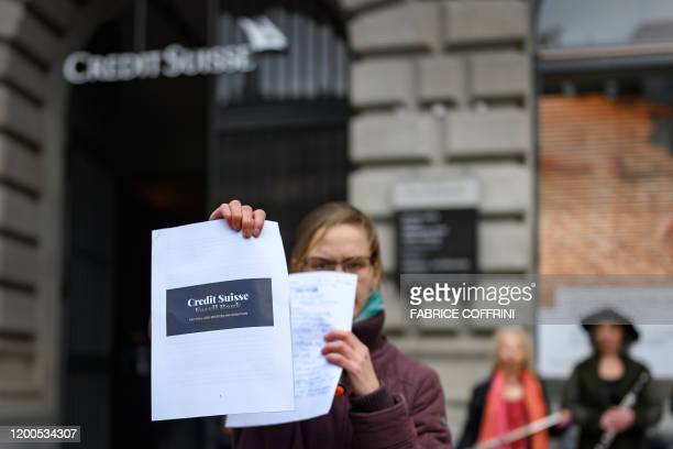 Climate activist holds a report during a protest against Swiss bank Credit Suisse on February 13 in Zurich, as the group holds a meeting to present...