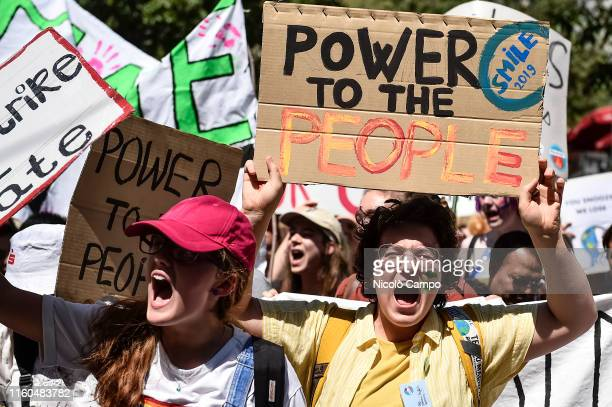 A climate activist holds a sign reading 'Power to the people' during a Fridays For Future strike for climate protection that is part of 'SMILE for...