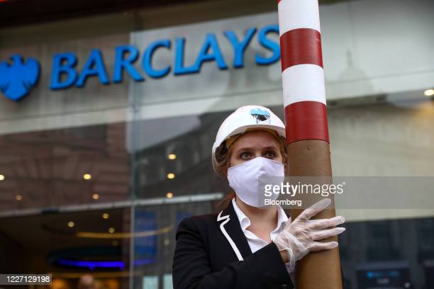 A climate activist holds a smoke stack outside a Barclays Plc bank branch in Piccadilly in London UK on Wednesday July 15 2020 Climate activists took...