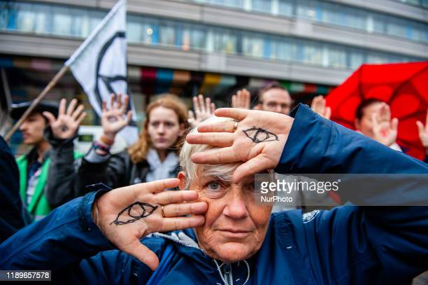 A climate activist is showing her hands with eyes painted on them during a demonstration in support of the Urgenda case that took place in front of...
