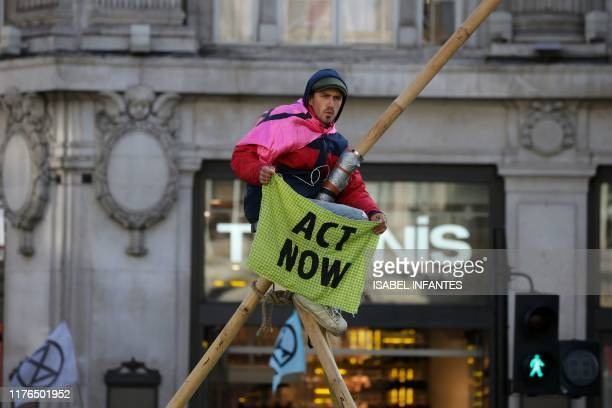 A climate activist perches on a makeshift structure in Oxford Street during the twelfth day of demonstrations by the climate change action group...
