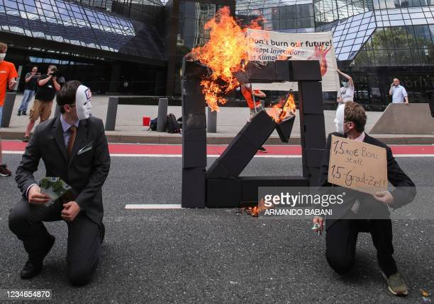Climate activists dressed up as bankers pose in front of a burning Deutsche Bank logo in front of the bank's headquarters during a demonstration...