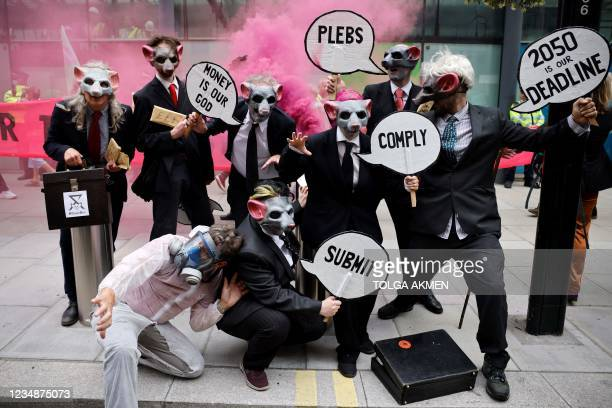 Climate activists from Extinction Rebellion wear rat masks as they protest during the group's 'Impossible Rebellion' series of actions, outside the...
