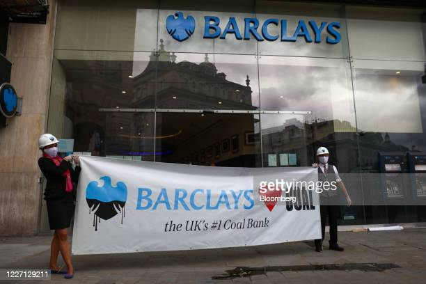 Climate activists from Fund our Future and Fossil Free London campaigns hold a banner outside a Barclays Plc bank branch in Piccadilly in London UK...