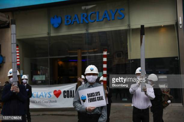 Climate activists from Fund our Future and Fossil Free London campaigns hold smoke stacks outside a Barclays Plc bank branch in Piccadilly in London...