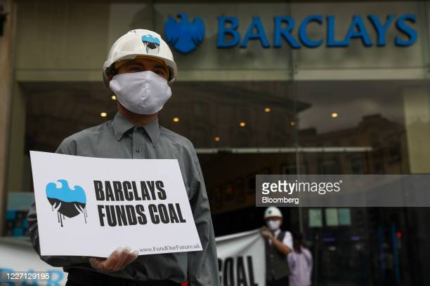 Climate activists from Fund our Future and Fossil Free London campaigns hold placards outside a Barclays Plc bank branch in Piccadilly in London UK...