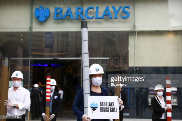 Climate activists from Fund our Future and Fossil Free London campaigns hold placards and smoke stacks outside a Barclays Plc bank branch in...