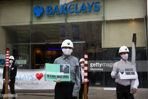 Climate activists from Fund our Future and Fossil Free London campaigns stand with placards and smoke stacks outside a Barclays Plc bank branch in...