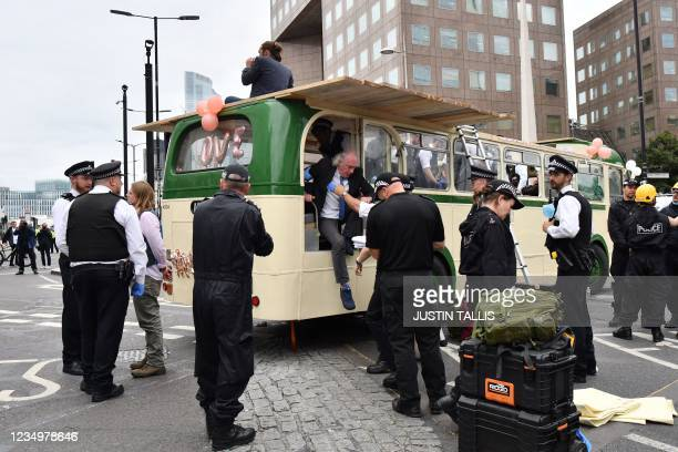 Climate activists from the Extinction Rebellion group, begin exiting a vehicle blocking the road over London Bridge in central London on August 31,...