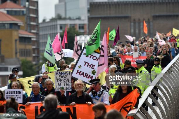 Climate activists from the Extinction Rebellion group cross the Millennium bridge in central London on September 2, 2021 during the group's...