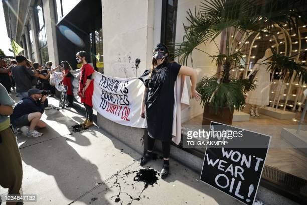 Climate activists from the Extinction Rebellion group demonstrate outside Selfridges store in central London on August 24, 2021 against the use of...