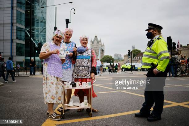 Climate activists from the Extinction Rebellion group pose with a tea service next to a police officer in the road leading to Tower Bridge in central...