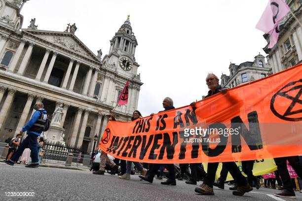 Climate activists from the Extinction Rebellion group walk past St Paul's cathedral in central London on September 2, 2021 during the group's...