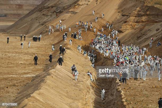 Climate activists from the group 'Ende Gelaende' charge across a ditch past riot police into the Hambach openpit coal mine on November 5 2017 near...
