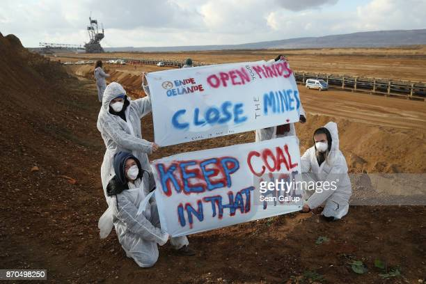 Climate activists from the group Ende Gelaende pose with banners at the edge of the Hambach openpit coal mine during a protest march on November 5...