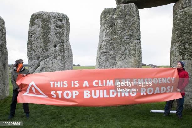 Climate activists hold a banner calling for an end to new road building during a Mass Trespass at Stonehenge on 5th December 2020 in Salisbury,...