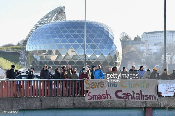 Climate activists hold banner reading 'Save the climate Smash capitalism' during a protest in Paris on December 12 2017 as French President Emmanuel...