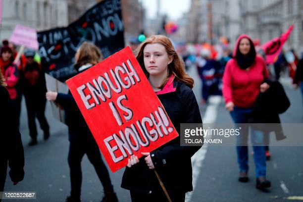 Climate activists hold placards as they march during a protest organized by the climate change action group Extinction Rebellion, in London, on...
